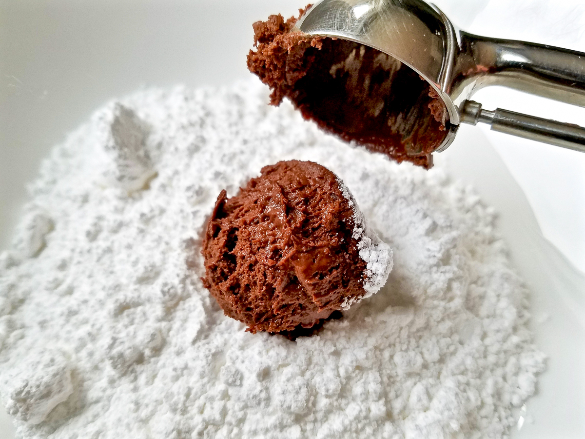 Rolling a ball of chocolate dough with powdered sugar.
