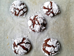 Five baked chocolate crinkle cookies on a baking sheet.