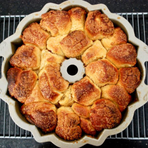 Baked monkey bread cooling in pan on rack.