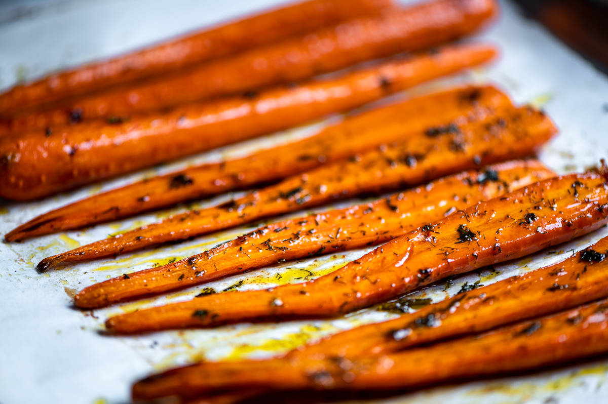Angle view of caramelized carrots on a baking sheet.