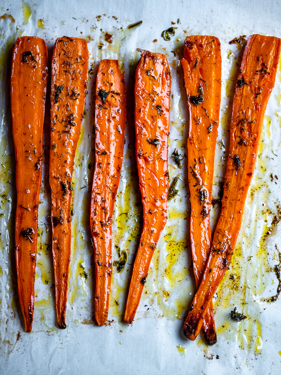 Carrots displayed as legs on a baking sheet.