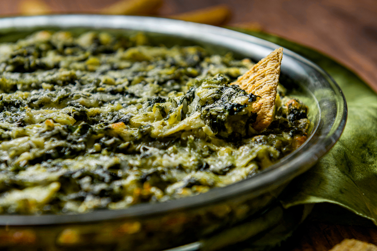 A cracker dipped into a bowl of spinach artichoke dip.