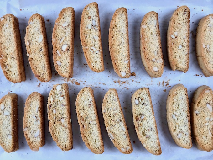 Baked sliced almond biscotti on a baking sheet.