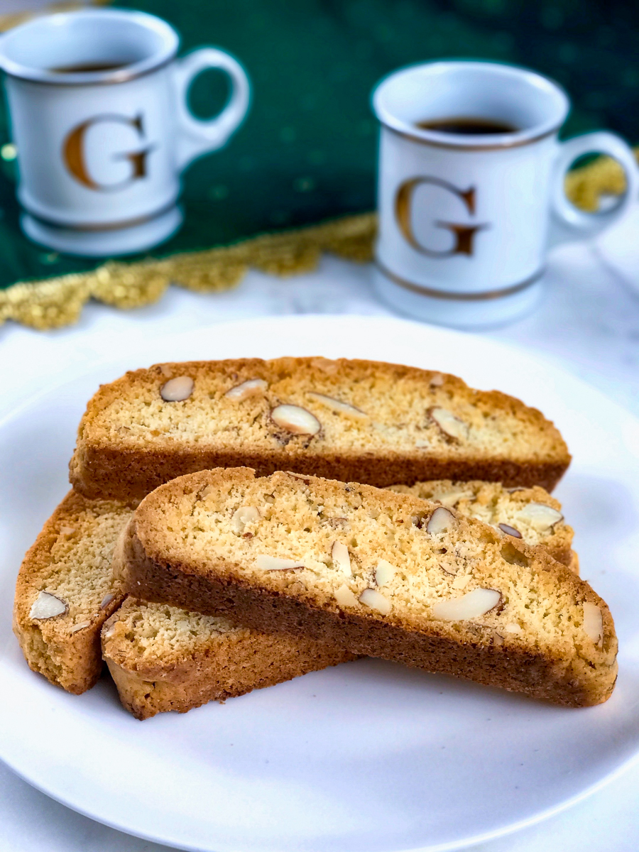 Almond biscotti on a white plate with cups of espresso in back.