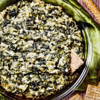 Cheesy spinach artichoke dip surrounded by crackers.