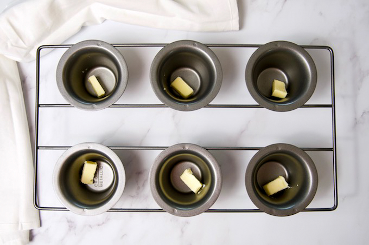 Popover pan with cubes of butter in molds.