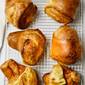 Six big golden popovers on a rack.
