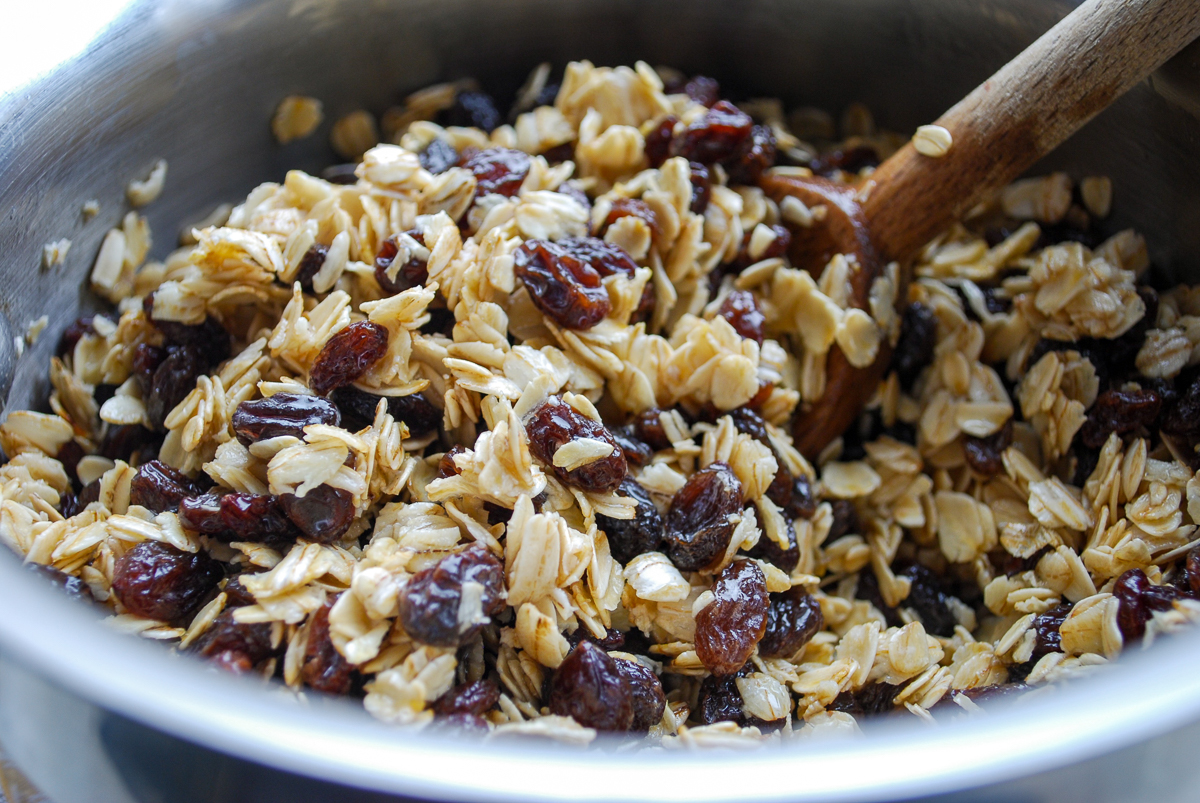 Mixing oats and raisins in a pan.