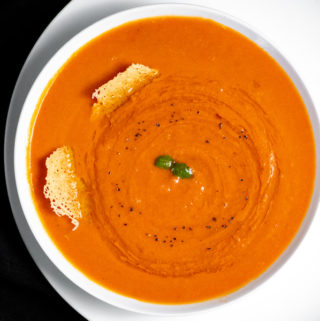 A white bowl of creamy tomato soup with 2 pieces of frico cheese.