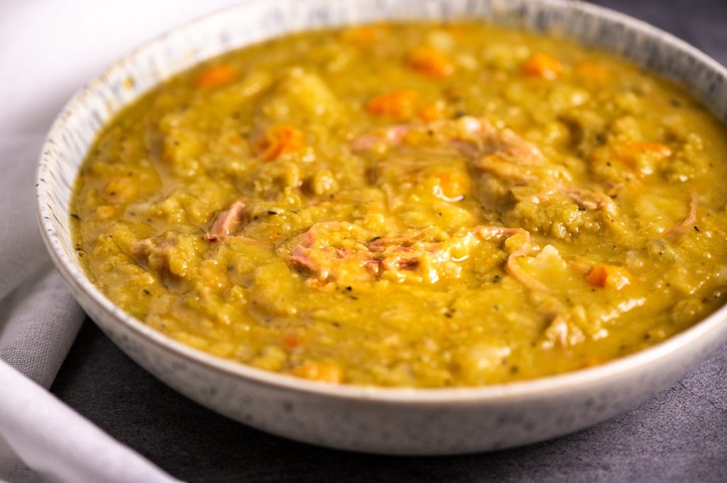 A closeup view of a bowl of split pea and ham soup.