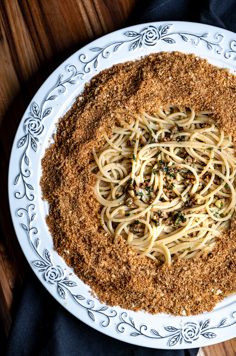 Spaghetti surrounded with toasted breadcrumbs on a round platter.