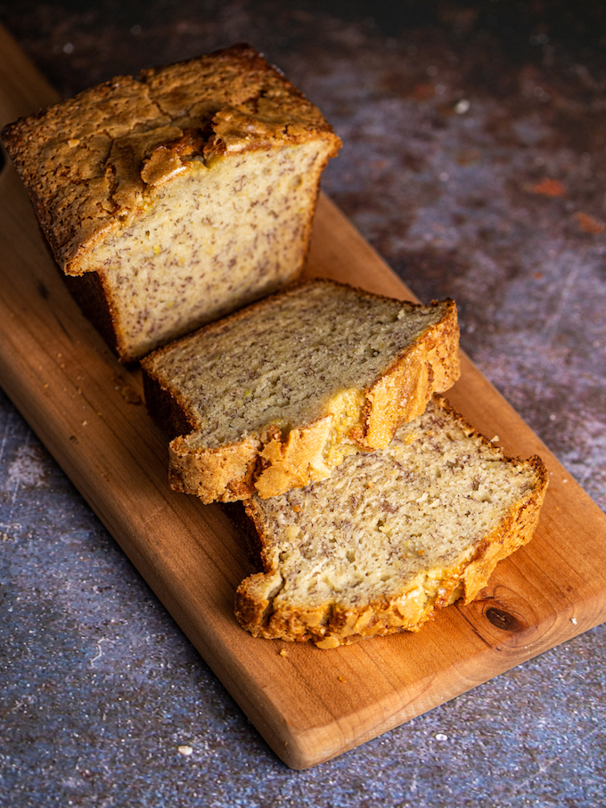 Banana bread with two slices on a cutting board.
