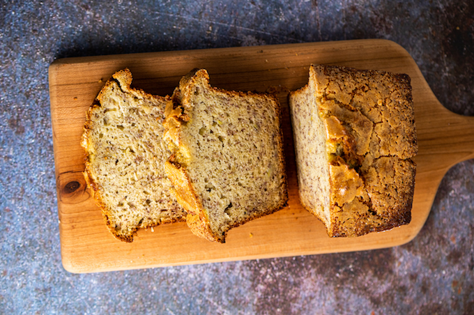 Horizontal view of sliced banana bread on a cutting board.