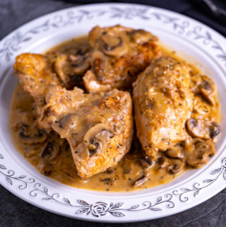 A platter of chicken and mushrooms covered in mushroom gravy.