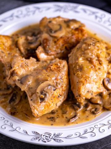 A platter of chicken and mushrooms covered in mushroom gravy.