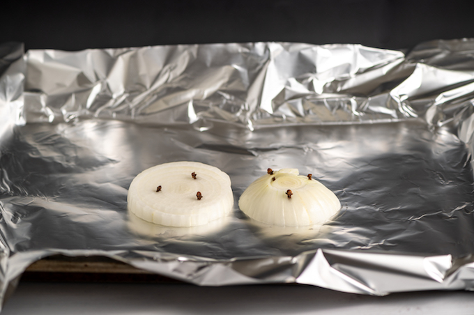 Two slices of onion stuck with cloves on foil on a baking sheet.