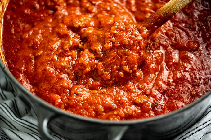 A spoonful of sauce from the pot.