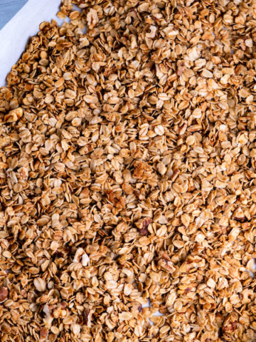 Maple walnut granola already baked on a baking sheet.