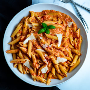 A bowl of penne alla vodka with shaved Parmesan.