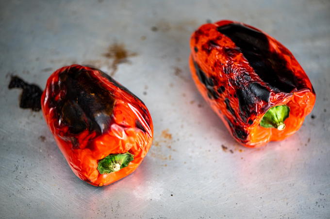 Roasted red peppers on a baking sheet.