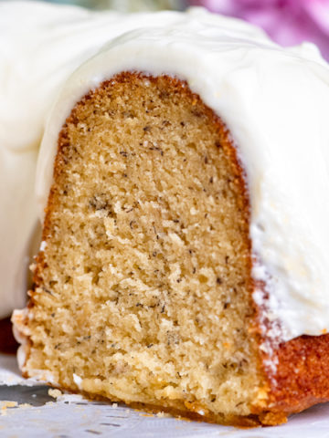 Closeup of a slice of banana bundt cake with cream cheese icing.