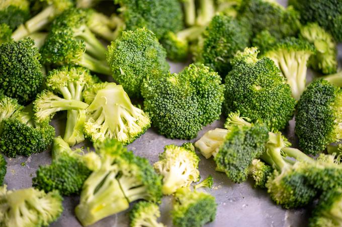 Broccoli florets scattered on a baking sheet.