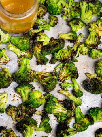 Charred broccoli tossed with Italian dressing on a baking sheet.