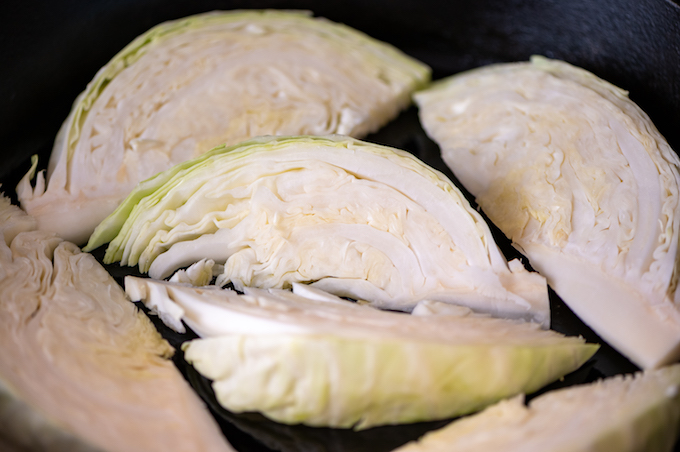 Cabbage wedges in a cast iron skillet.