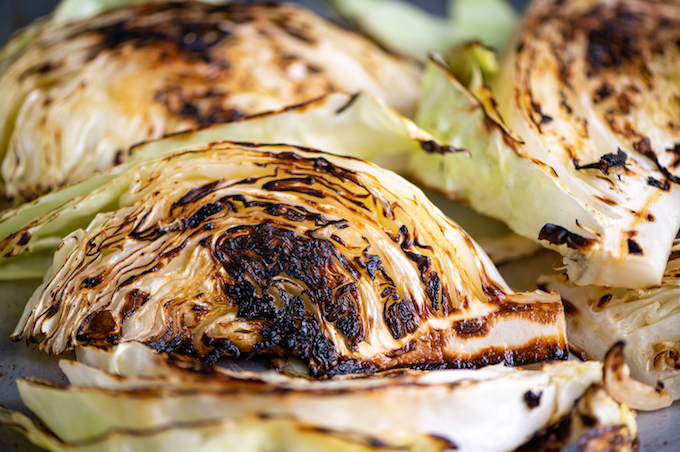 Charred cabbage wedges on a baking sheet.