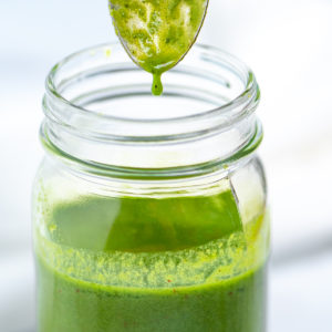 A jar of basil vinaigrette with a spoon over it and a drop of vinaigrette falling back into the jar.