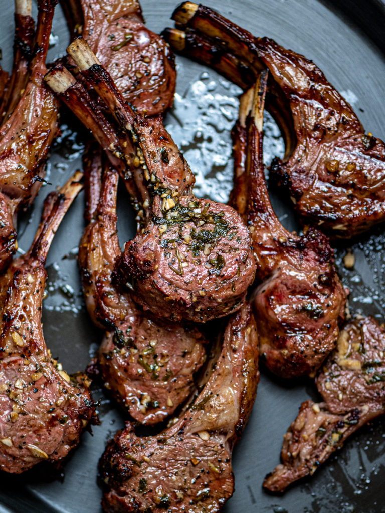 Grilled lamb chops on a black platter.