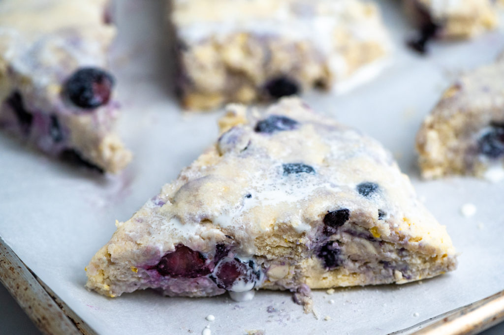 Closeup of a blueberry scone ready to be baked on a baking sheet.