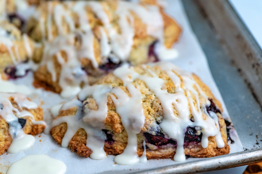 Closeup of a blueberry cream scone drizzled with glaze on a baking sheet.