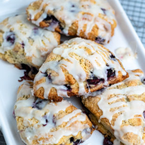Five blueberry cream scones piled on a baking sheet.