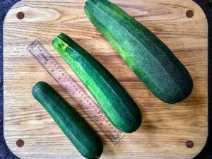 Different sized zucchini on a cutting board.