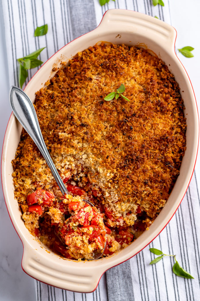 Baked tomato casserole with a spoonful ready to be scooped out.