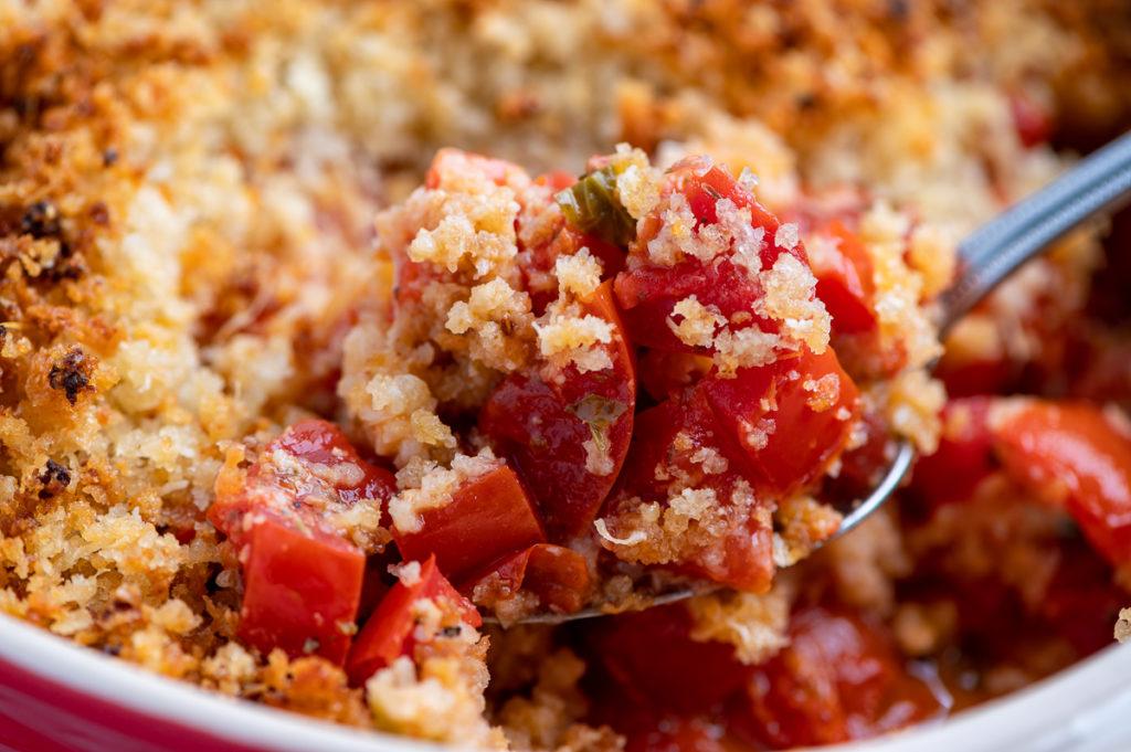 A closeup of a spoonful of tomato casserole.