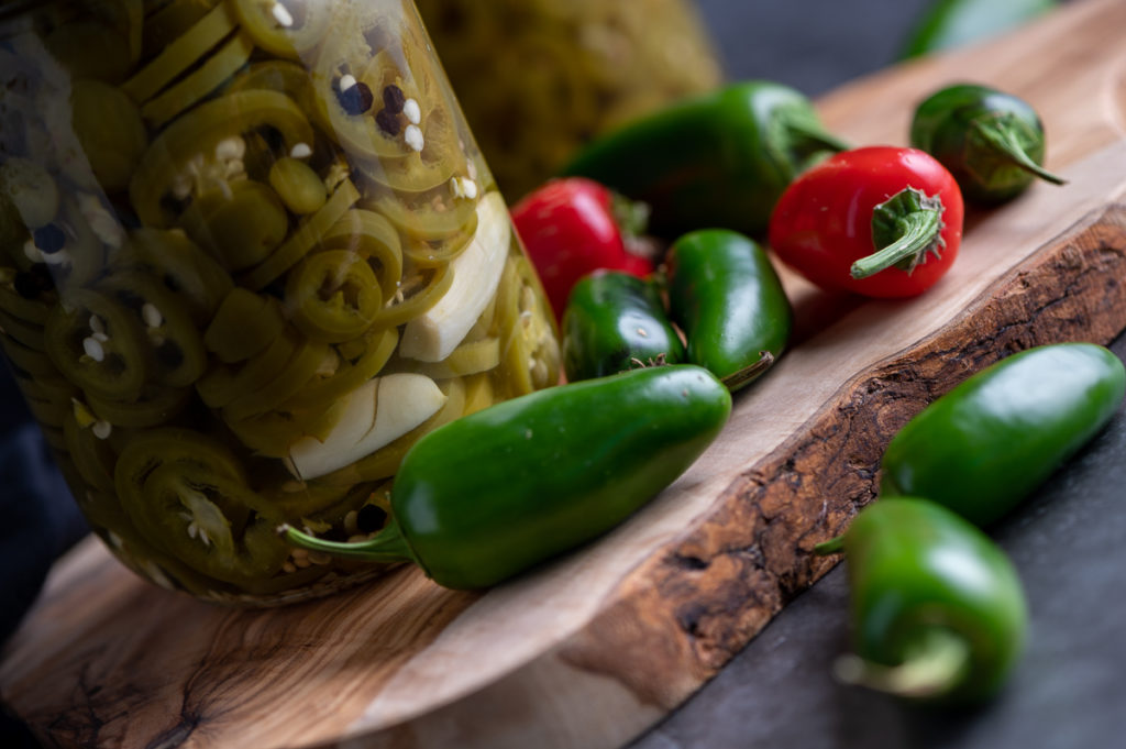 An angled view of a jar of pickled jalapeños and scattered jalapeños on a board.