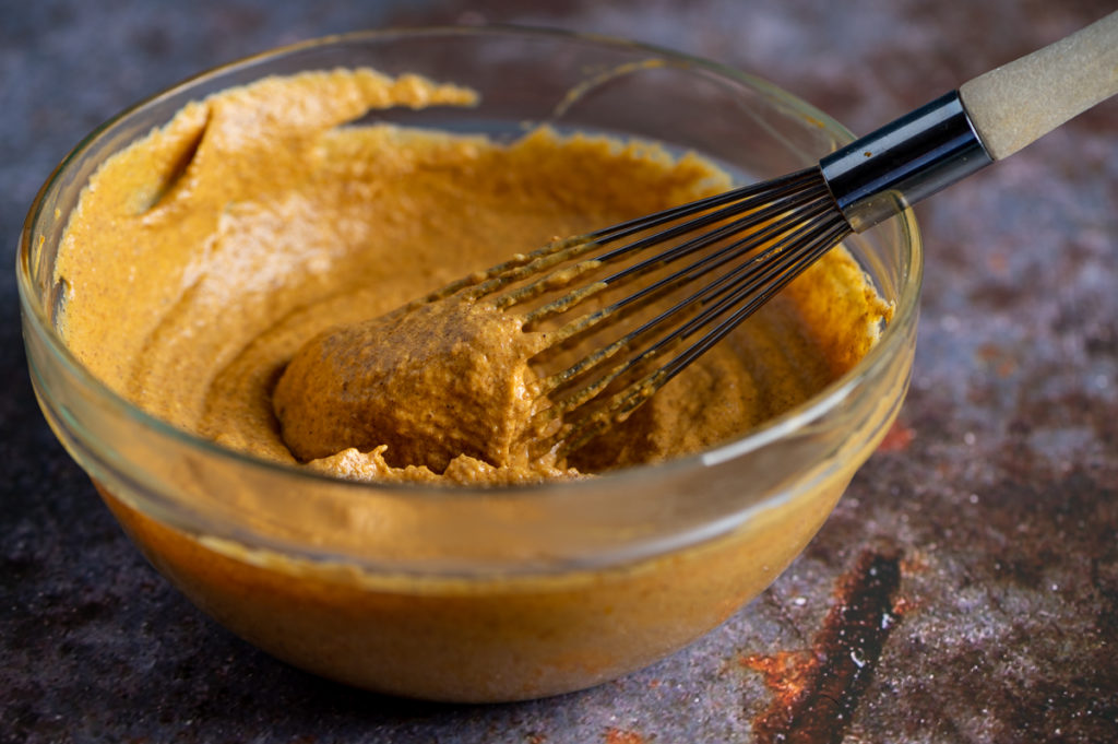 A mixing bowl full of pumpkin dip whisked together.
