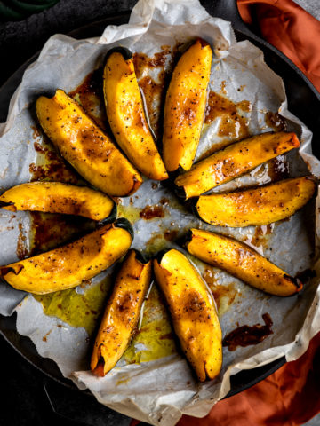 Roasted acorn wedges arranged in a circle in a cast iron skillet.