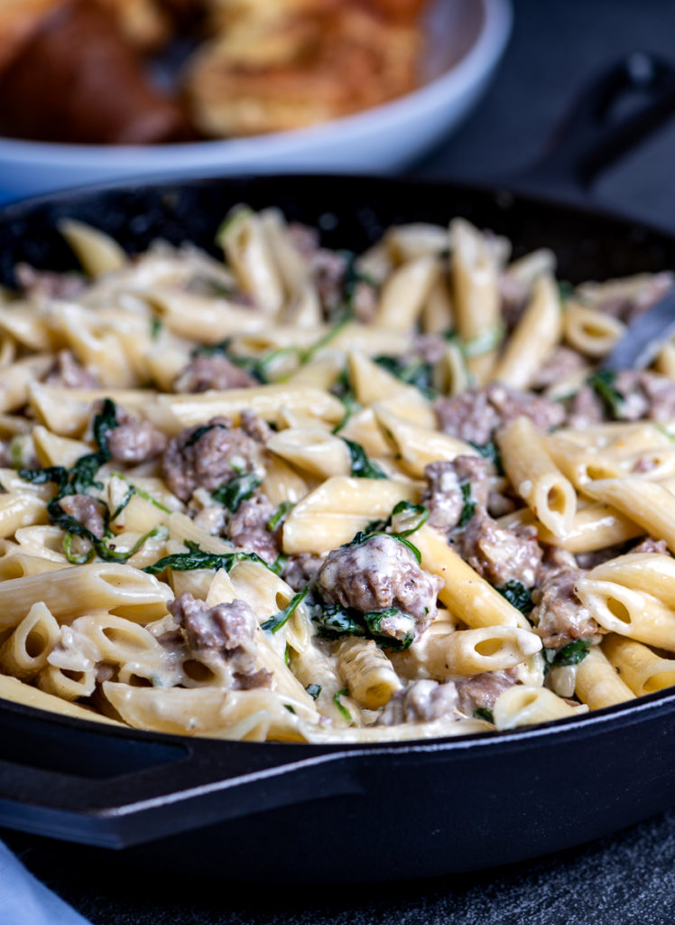 A skillet of cheesy sausage pasta.