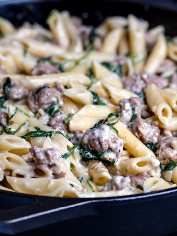 A cast iron skillet filled with creamy cheesy pasta with spinach and sausage.
