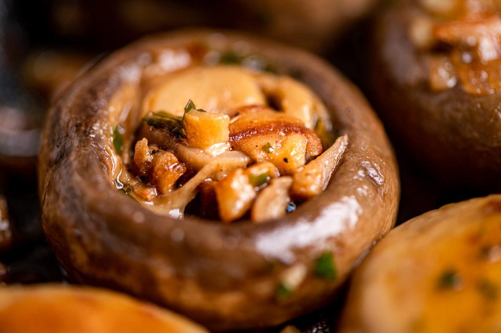 A closeup of a sautéed mushroom with garlic and shallots.