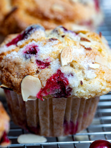 A cranberry muffin on a cooling rack with more in background.