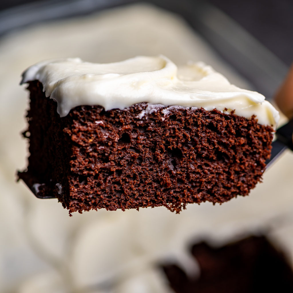 A slice of chocolate cake with cream cheese frosting.