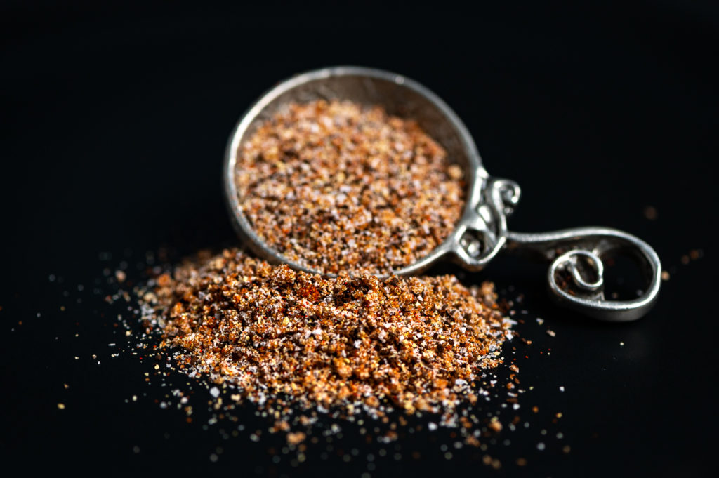 A tablespoon on its side filled with some coffee rub with some spilling over .