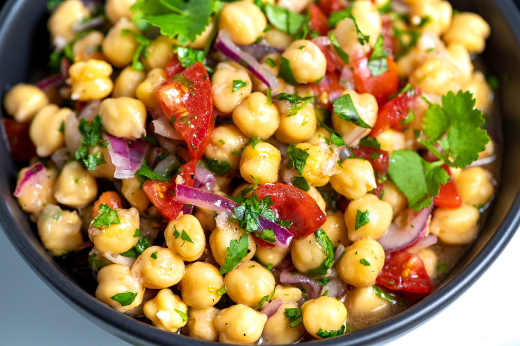 A closeup of chickpea salad in a black bowl.