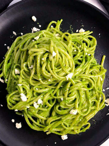 A black plate of pasta tossed with Peruvian pesto with bits of feta on top.