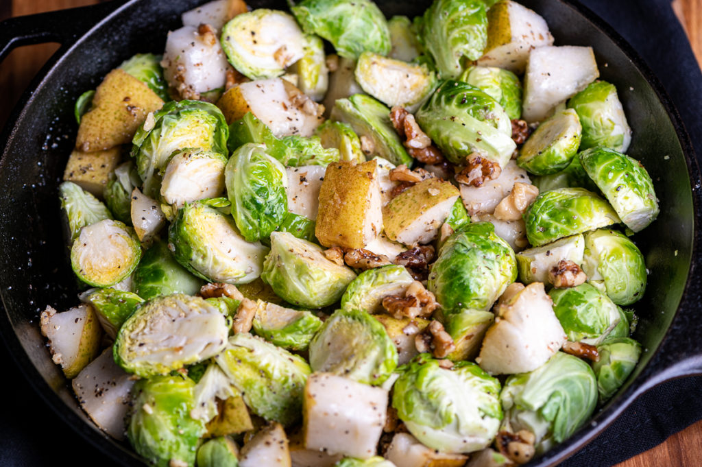 Sliced Brussels sprouts, chopped pear and walnuts in a skillet.