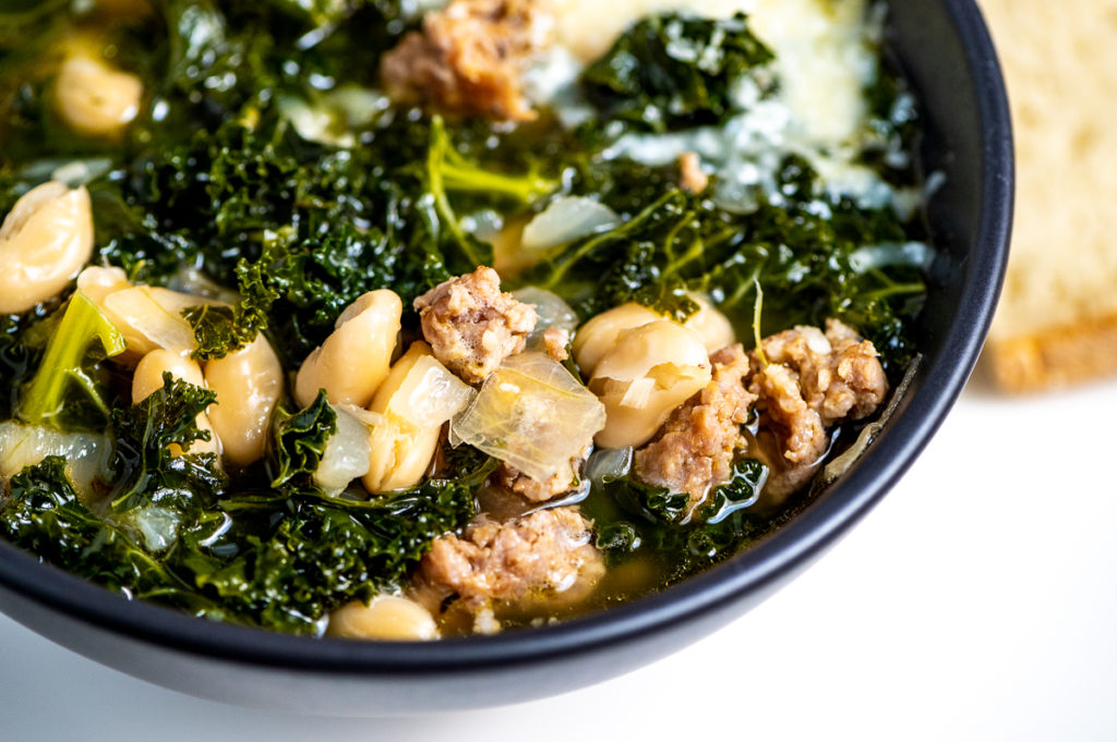 A black bowl of kale soup with white beans and sausage.